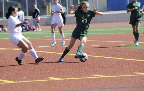 Varsity Soccer member Claire Glendening '18 swiftly dribbles the soccer ball across the field, and away from opponents during a game.