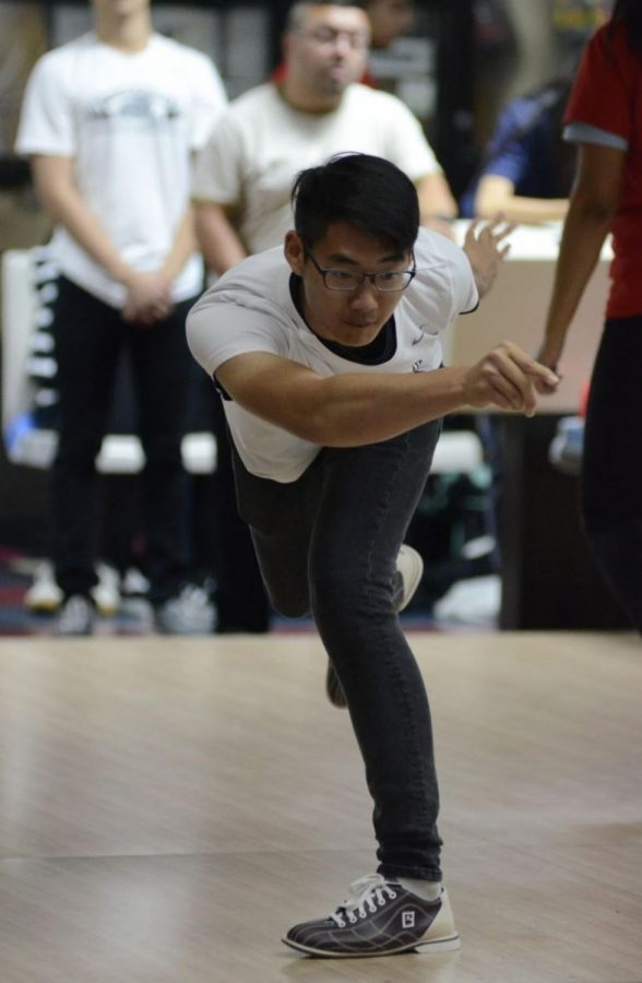 As the Varsity bowling team takes the lead in their game, senior Baron Huang finishes his strides, which sent the ball hurling towards the pins, straight down the middle of the alley