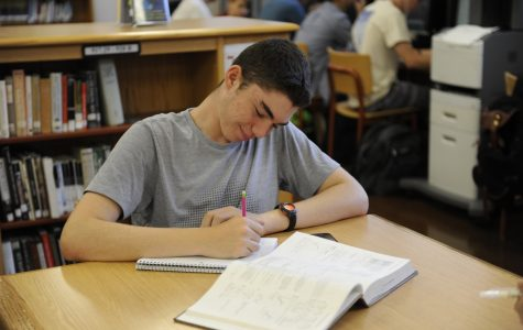 Morgan Krell '18 keeps on top of his coursework during his senior year by taking the time to complete homework in the school's library.