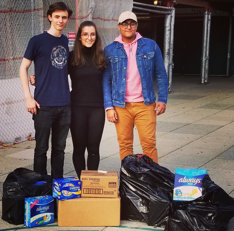 John Aidan Feighery '19, Chloe Frajmund '19, and Alif Matin '19 stand in front of the donated pads and tampons before giving them to Legion of Goodwill.