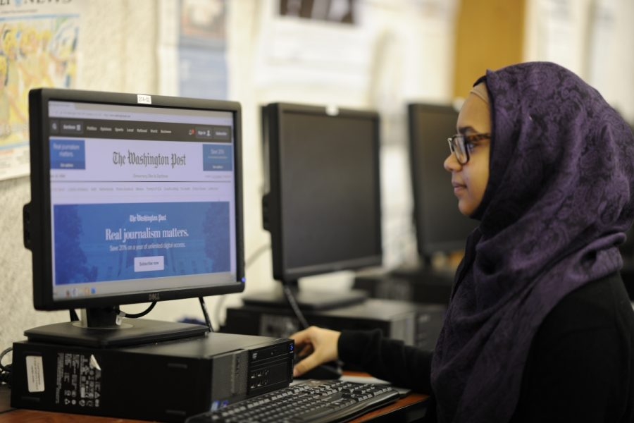 Student journalist Nuzat Zaman reads a recent edition of 'The Washington Post.'