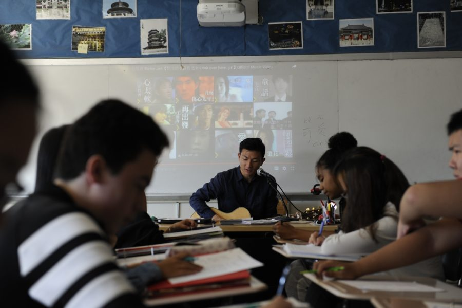 Mr. Qiu, Chinese teacher, instructs  his students in Chinese by singing  a popular song in the language.