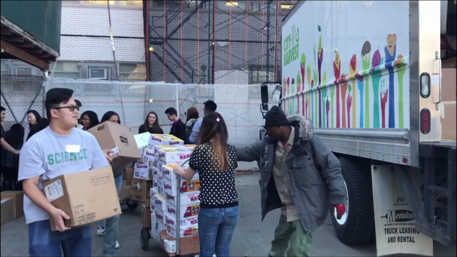 The SO and City Harvest representatives work hard together to cart heavy packages of cans to the truck for donation.