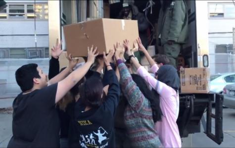 The SO collaboratively hoists a heavy box onto the City Harvest truck.