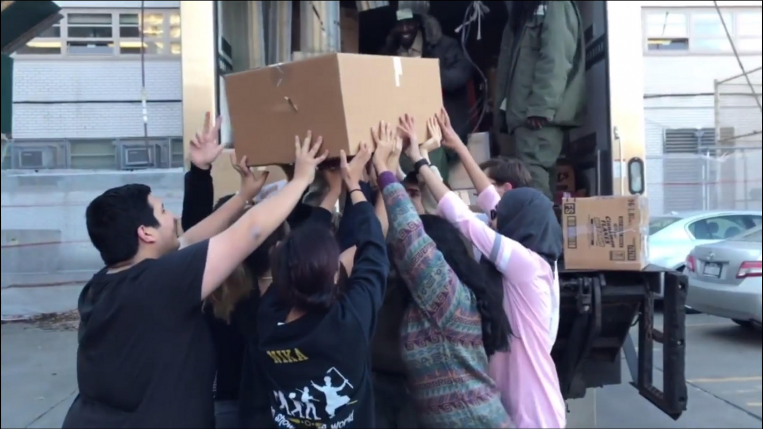 The SO collaboratively hoists a heavy box onto the City Harvest truck.