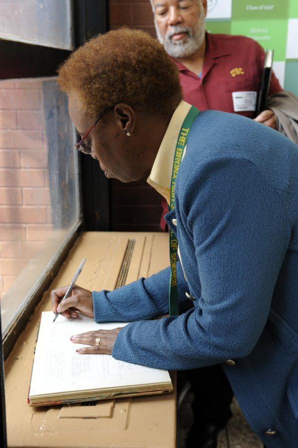 Wanda Austin signs her name in the Hall of Fame book.