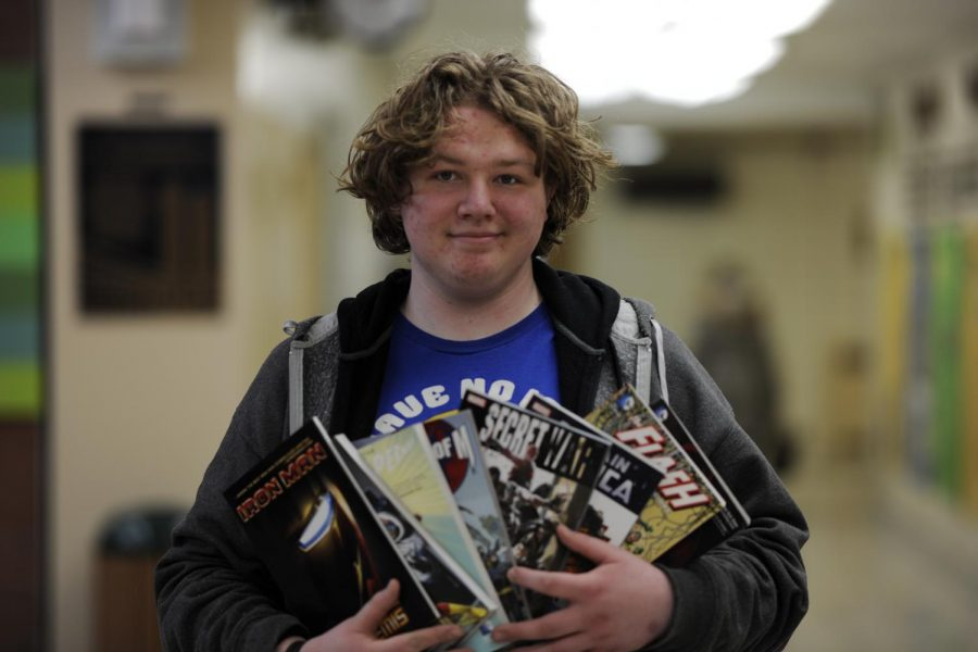 Gearod Murphy '19 with a slew of Marvel and DC superhero comics, including The Flash, Iron Man, Captain America, and The Avengers.
