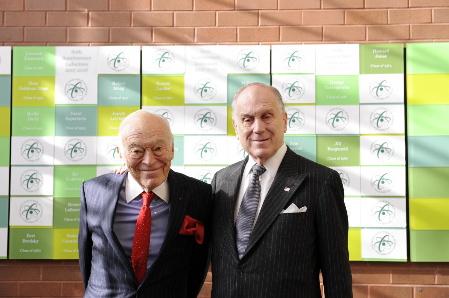 The Lauder brothers pose in front of the Bronx Science Hall of Fame  following their formal induction.