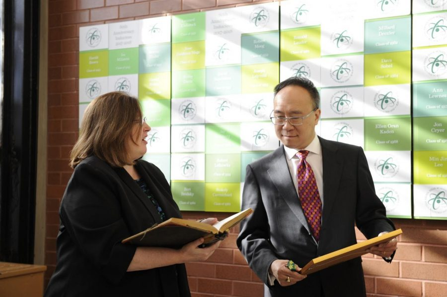 King Lai humbly receives gifts give by the Principal and stands in front of the prestigious alumni wall.