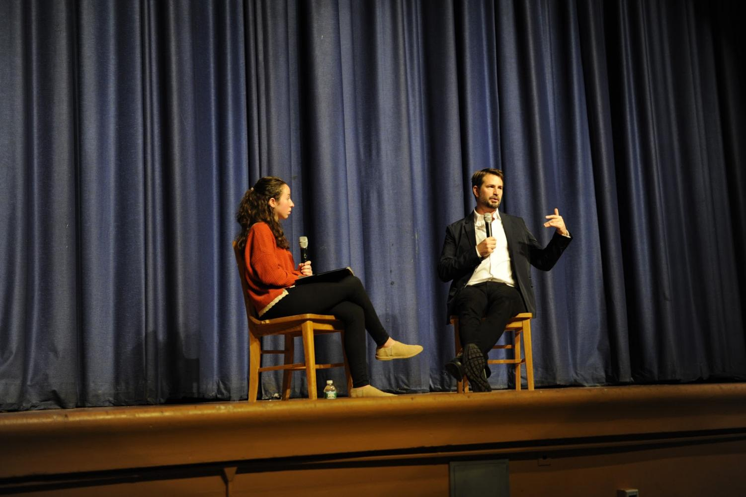 Anastasia Koutavas '18 interviews Mr. Boal in front  of the student body in the auditorium.