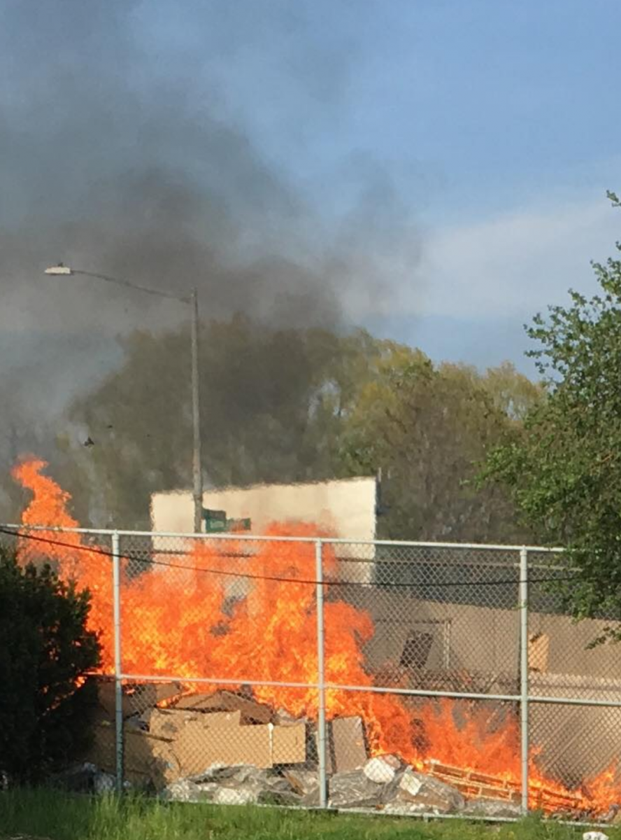 The fire quickly spread through the gated-in pile of trash.