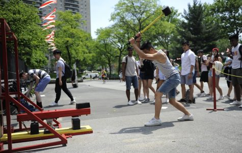 Science student takes a long swing at the High Striker during the S.O. Carnival.