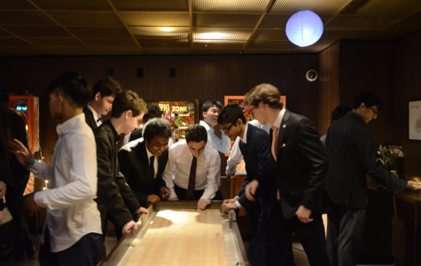 A group of juniors crowd around a table hockey game with excitement during Junior Prom.