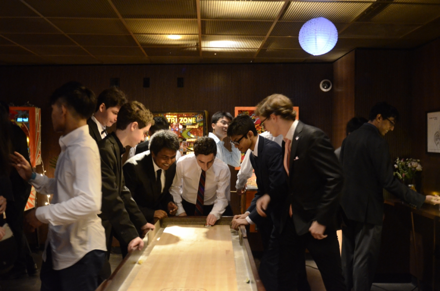 A+group+of+juniors+crowd+around+a+table+hockey+game+with+excitement+during+Junior+Prom.
