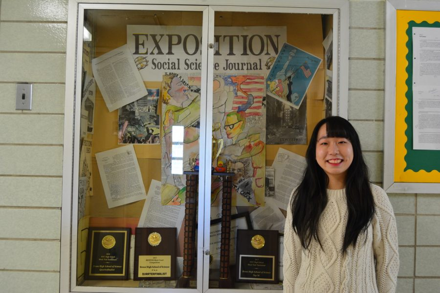 Mian Hua Zheng '19 stands next to Exposition's previous publications, hoping to improve the quality of this year's journal.