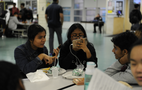 Students spend their lunch period watching shows on their iPhones.