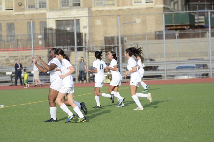 Girls Varsity Soccer Team celebrating a goal.