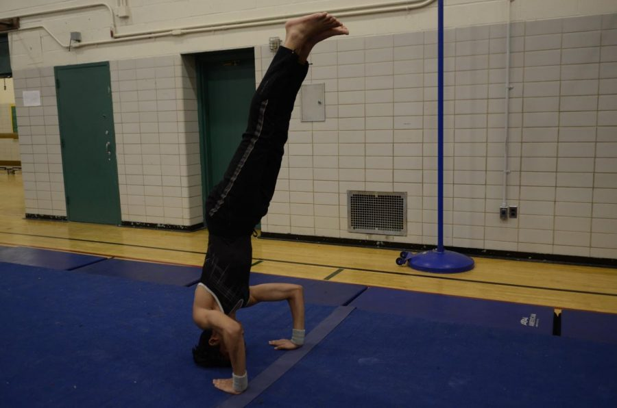 Rafi Talukder '20 performing a headstand during a meet in 2018.