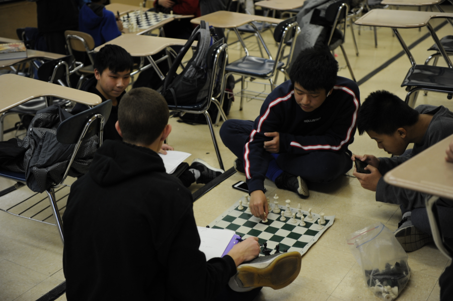"""A group of friends think through their next moves during a friendly chess match. Kyle Zhen '22, pictured, said, """"I think chess is a great game to play, and it's also really fun to beat your friends."""""""