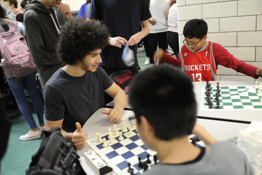 """""""Showing it Off: A group of elated students demonstrates the sport of chess at the annual club fair"""""""