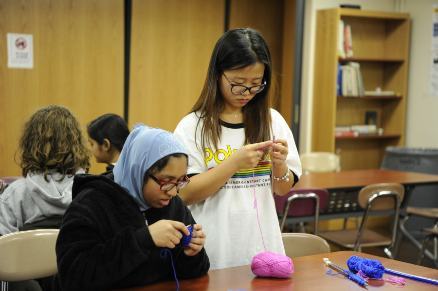 Vivien Lin '20 (center standing) is focusing as she learns how to knit
