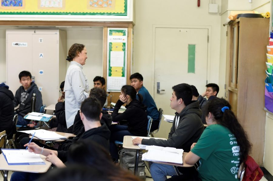 While lecturing to her students, Ms. Lerohl walks up and around with a warm smile on.