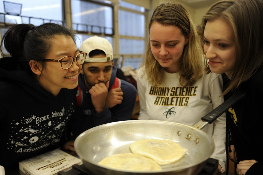 Members of the World Cooking Club gather round to intently watch a dish as it is cooked.