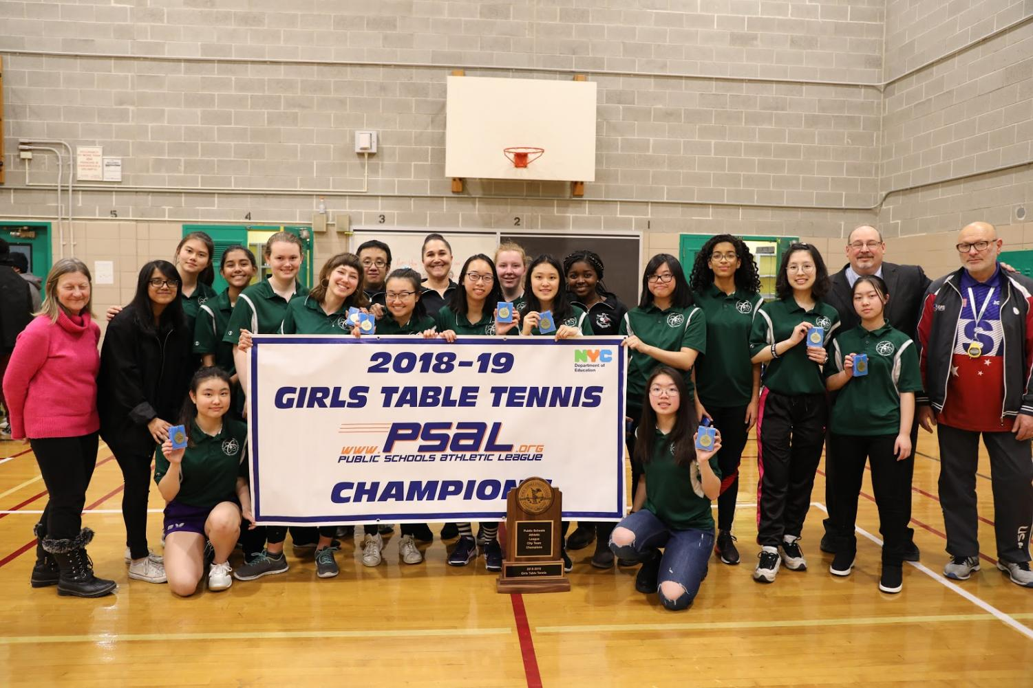 The Girls' Varsity Table Tennis team claim their  championship banner.