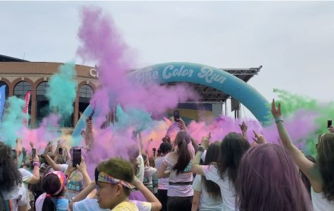 Runners collected at the stage to participate in color throws, filling the sky with rainbow colors.