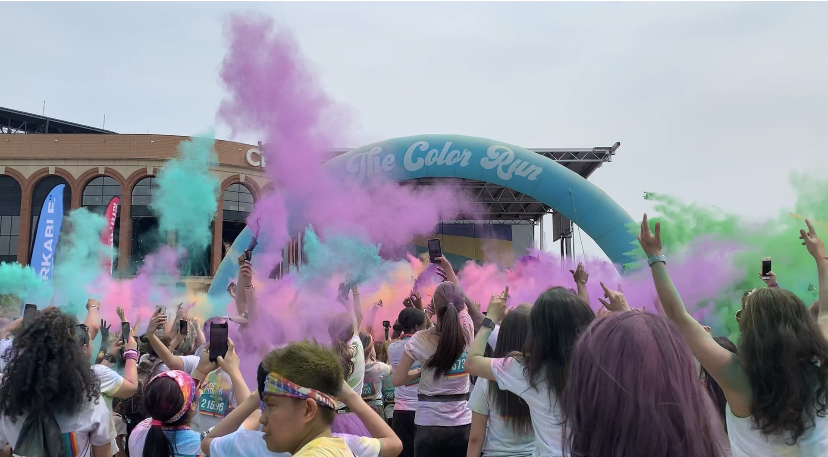Runners+collected+at+the+stage+to+participate+in+color+throws%2C+filling+the+sky+with+rainbow+colors.