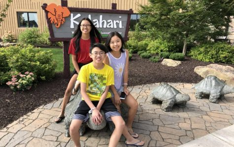 Sitting on a turtle in front of a conservation center, Joy, Eddy, and Julie Lin sit on a turtle on a family outing together.
