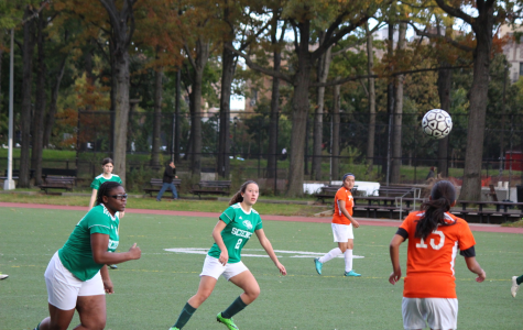 Members of the Bronx Science Girls' Varsity Soccer team lock their eyes on the ball while playing a game against another school.