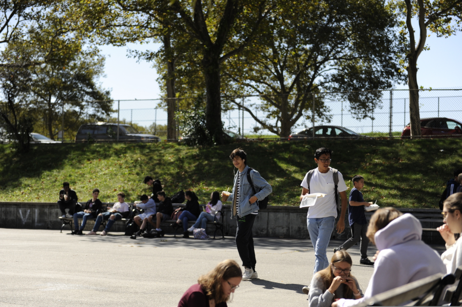 Students enjoy lunch in the courtyard on a sunny day out at Bronx Science.