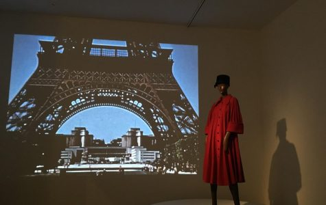 A model in long red coat  positioned in front of a projection  of the Eiffel Tower.