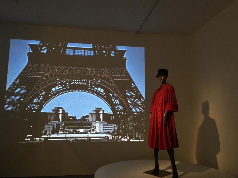 A+model+in+long+red+coat+%0Apositioned+in+front+of+a+projection+%0Aof+the+Eiffel+Tower.