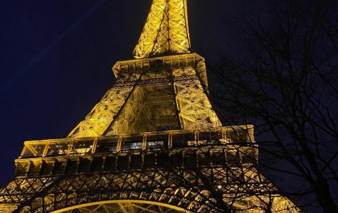 """The glowing, lit-up Eiffel Tower stands in front of a midnight blue sky. Sophie Poritzky '21 loves taking pictures from unconventional perspectives. She says, """"I love how photography can capture a really special moment and keep it forever, both physically and in my memory."""""""
