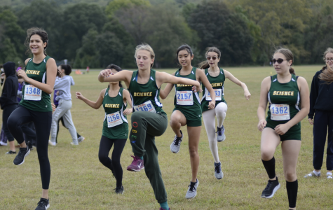 Ninth graders on the Girls' Cross Country team warm up together before a meet.