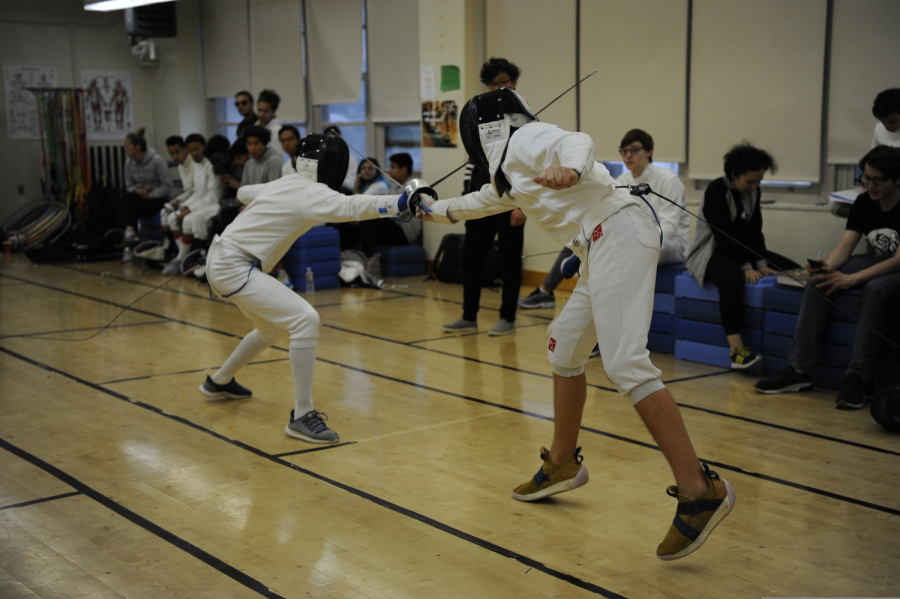 Student athletes take part in a fencing match, thrusting their swords.