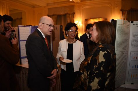 Dr. Donahue and her husband discuss the research projects with Dr. Jill Bargonetti on the night of the research competition.
