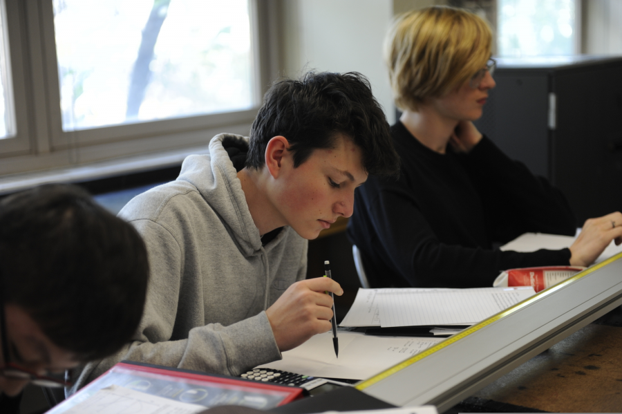 In AP Physics, students diligently record calculations while completing a lab.
