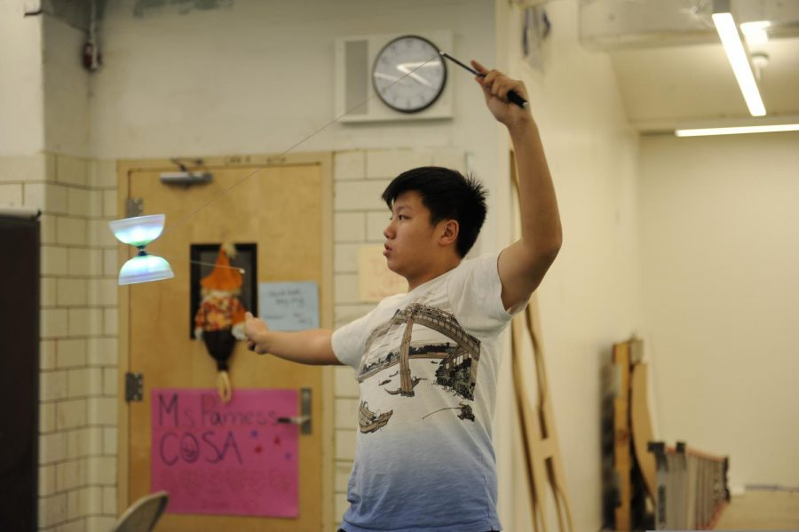 A student practices playing the Chinese yo-yo at Lunar New Year Productions Club.