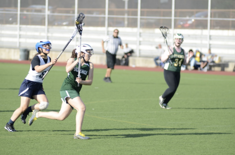 As Samantha Mayol '22 runs towards the goal during a Girls' Varsity Lacrosse meet, she looks for an opening to make her shot.