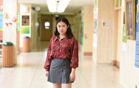 Sara Poon '21 embraces her unique sense of style by wearing an elegant red blouse, with a pleated skirt, finished off with some gold jewelry.