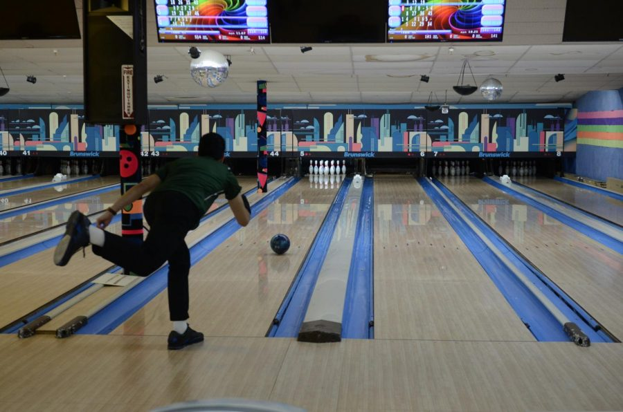 A student on the Boys' Bowling team shoots the ball down the alley!