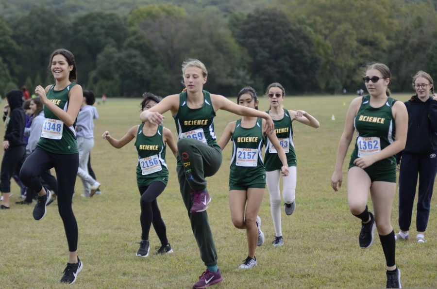 Students in Cross Country Girls' Varsity warm up together.