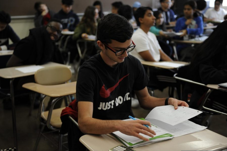 An eleventh grader flips through his notebook in Pre-Calculus.