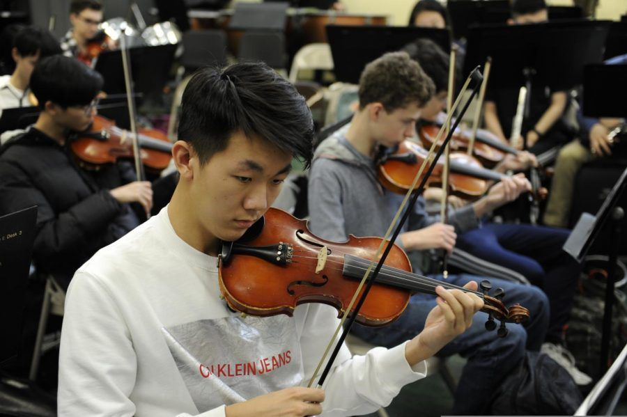 A student performs a musical piece on the violin during Orchestra.