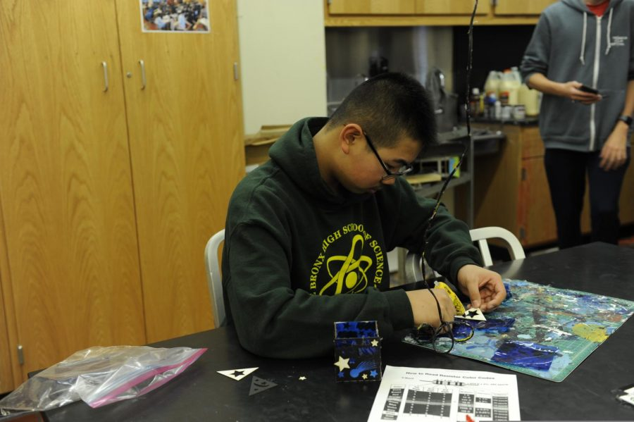 A student uses hot-glue to assemble the parts of his project.
