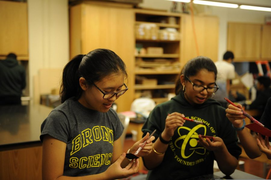 During Elements of Engineering, a group of freshman paint the pieces of their assignment.