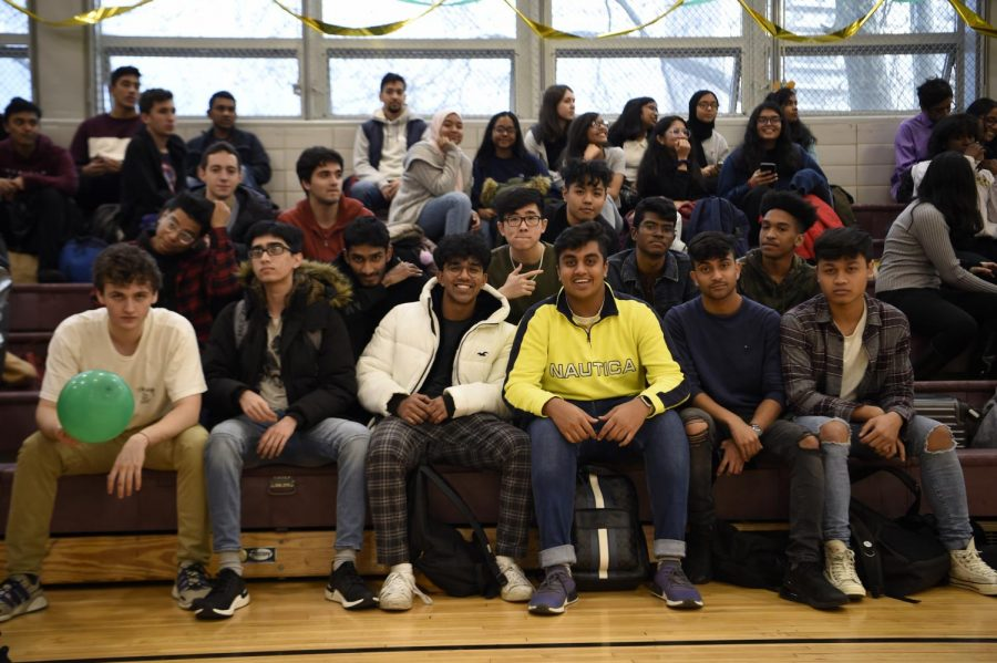 A group of students sit on the bleachers in the gym as the November 2019 Homecoming events begin.